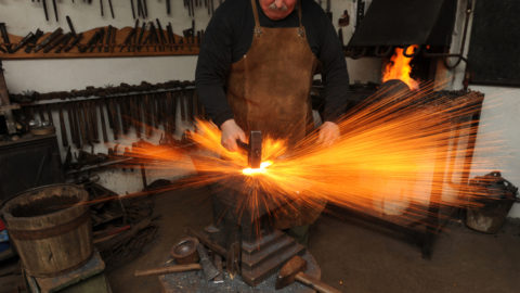a blacksmith working on a piece of metal with sparks flying